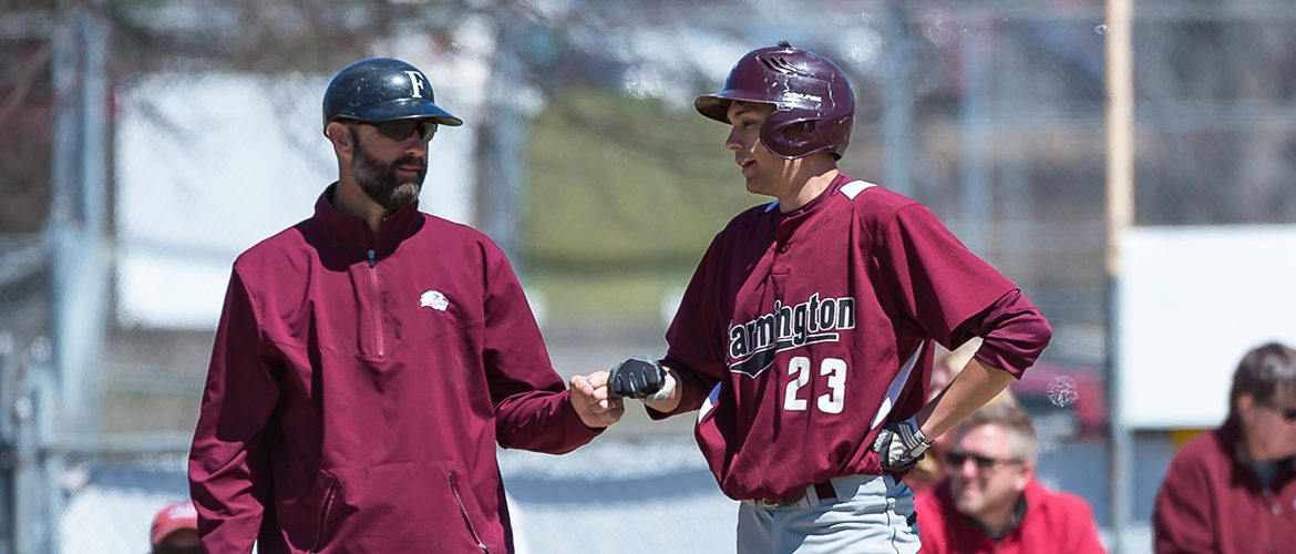 Baseball coach fist-bumping UMF baseball player