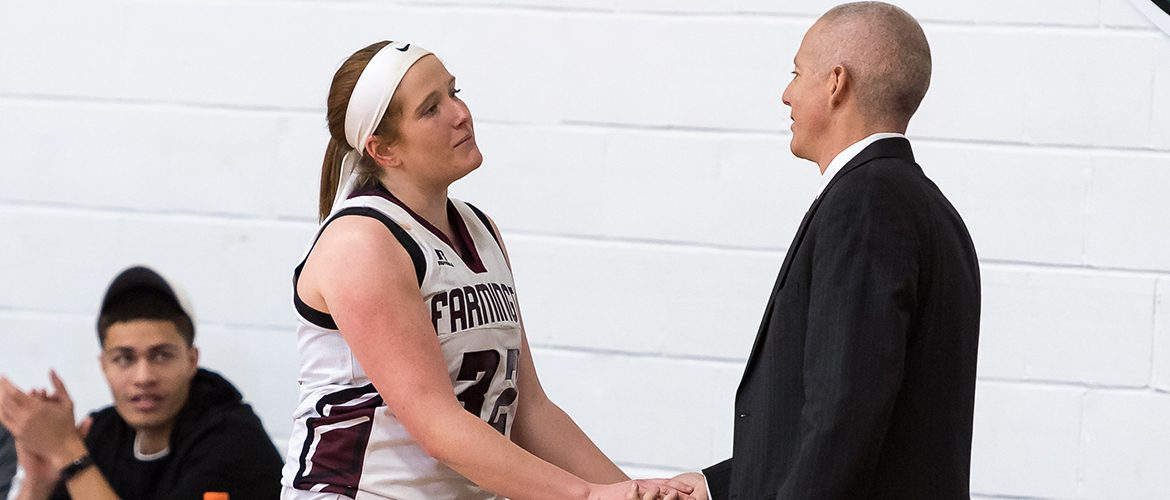 Women's basketball coach shaking hands with UMF women's basketball player