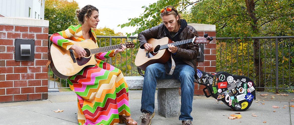 Male and female student playing guitars outdoors