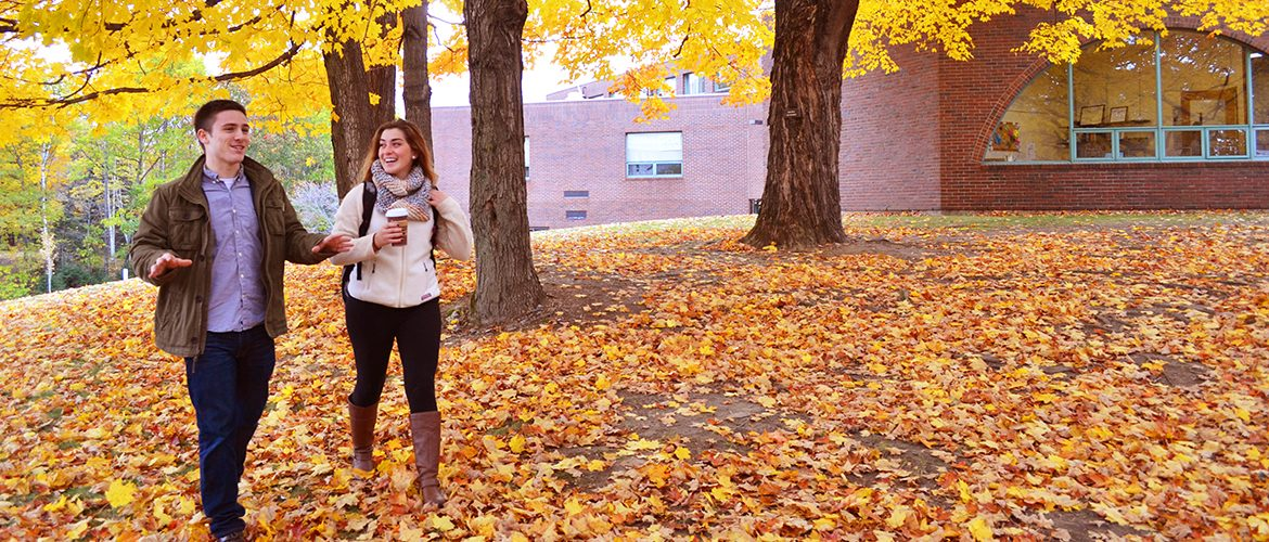 Male and female student walking in fall foliage