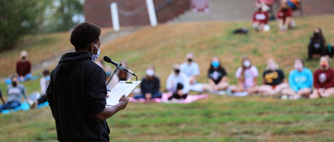 Student in mask giving a speech in the Amphitheatre