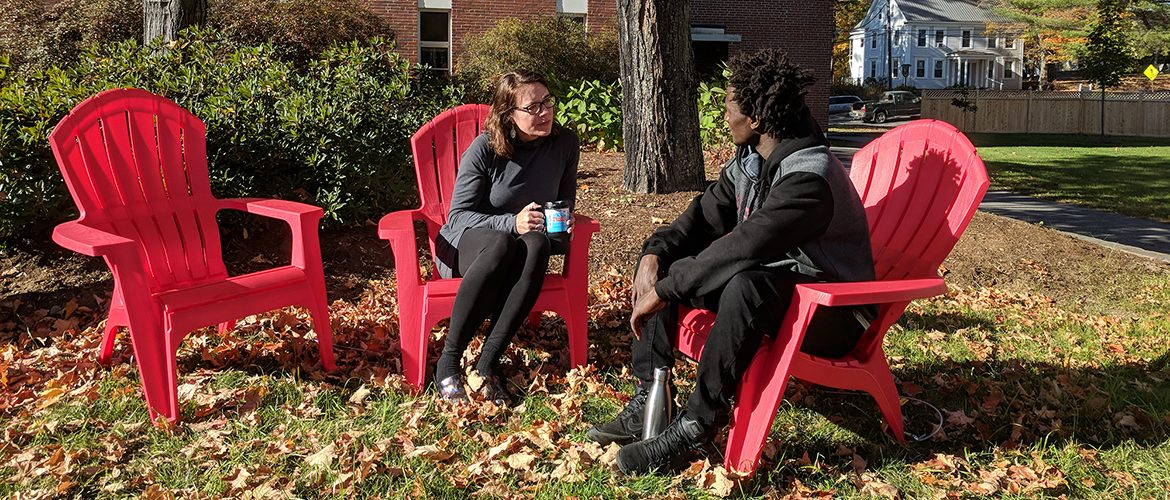 Professor and student chatting in campus courtyard