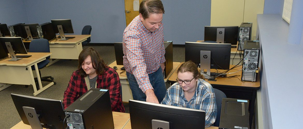 Professor working with students in computer lab classroom