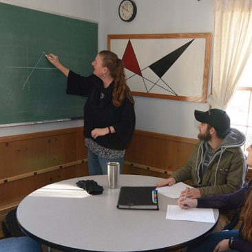 Professor working with students in a small group study space inside the Math and Computer Science Department building