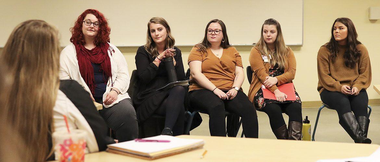 Graduate students talking to a classroom of undergrad students