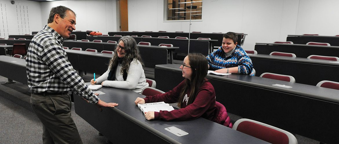 Professor talking with students in a lecture hall
