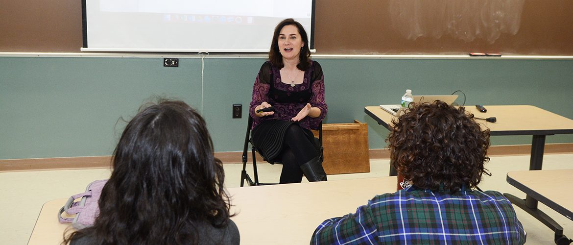 Professor talking with students in classroom