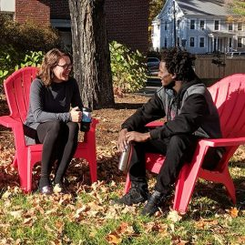 Professor and student talking outdoors in the campus courtyard
