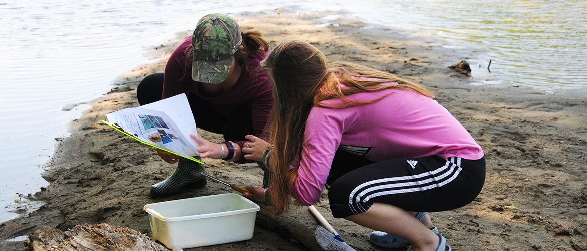 Two students conducting outdoor research at a river bank