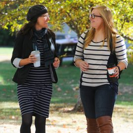 Professor and student walking outdoors on campus