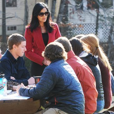 Students and professor in an outdoor class sitting at a picnic table