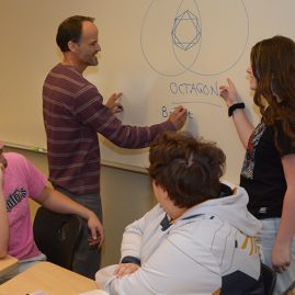 Professor working with students in a math class