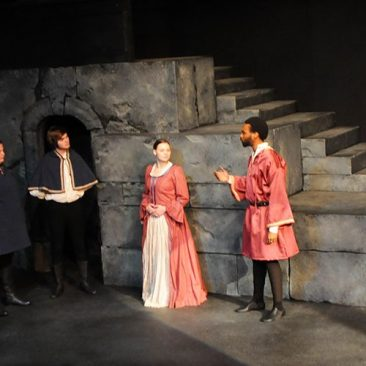 Four students acting on stage during theatre rehearsal