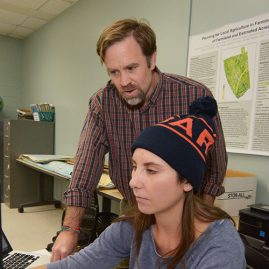 Professor working with a student in the Geographic Information Systems classroom