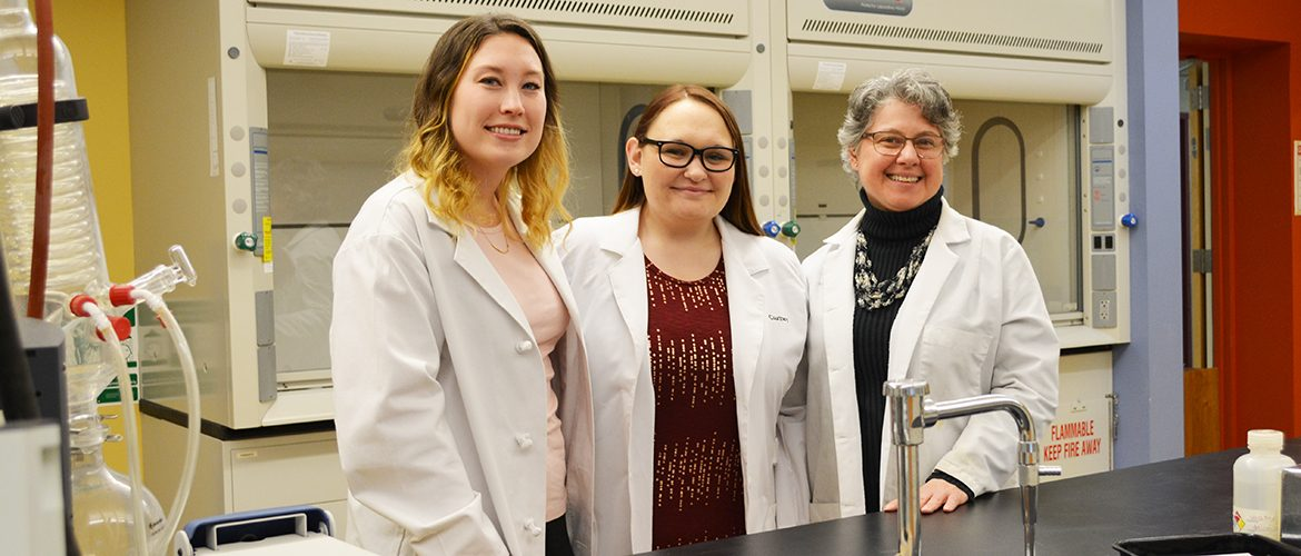 Female professor and two students smiling in chemistry lab