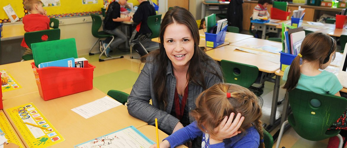 Woman-student teacher working with school child