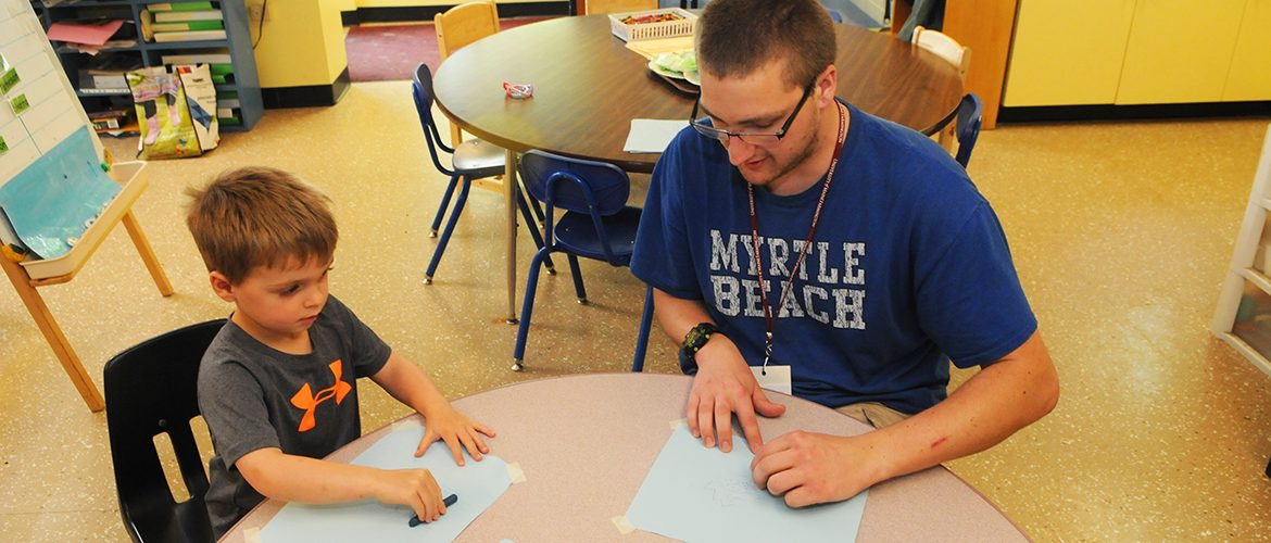 Male-student working with preschool child