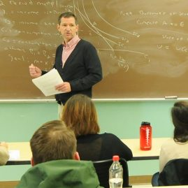 Male professor teaching classroom of students taking notes