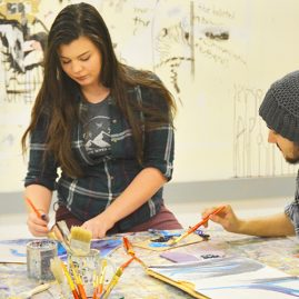 Two students painting in art studio