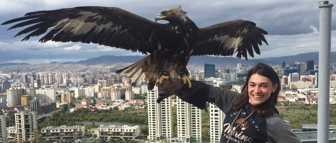 Student studying abroad holding a condor on her arm