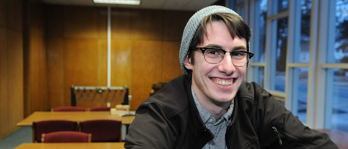 Male student with glasses smiling in student lounge
