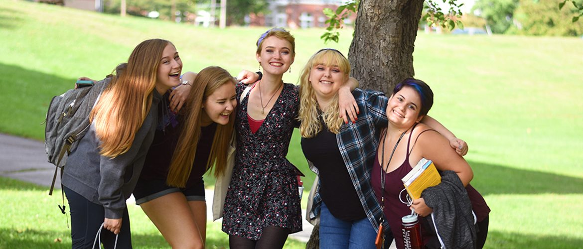 Group of students smiling outdoors at campus amphitheater