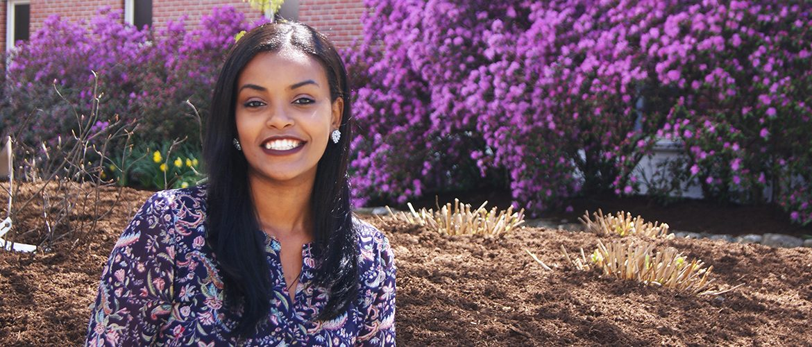 Woman student smiling in front of lilac bushes in campus courtyard