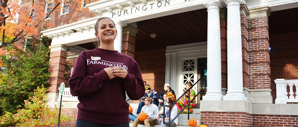 Woman student smiling in front of Purington Hall