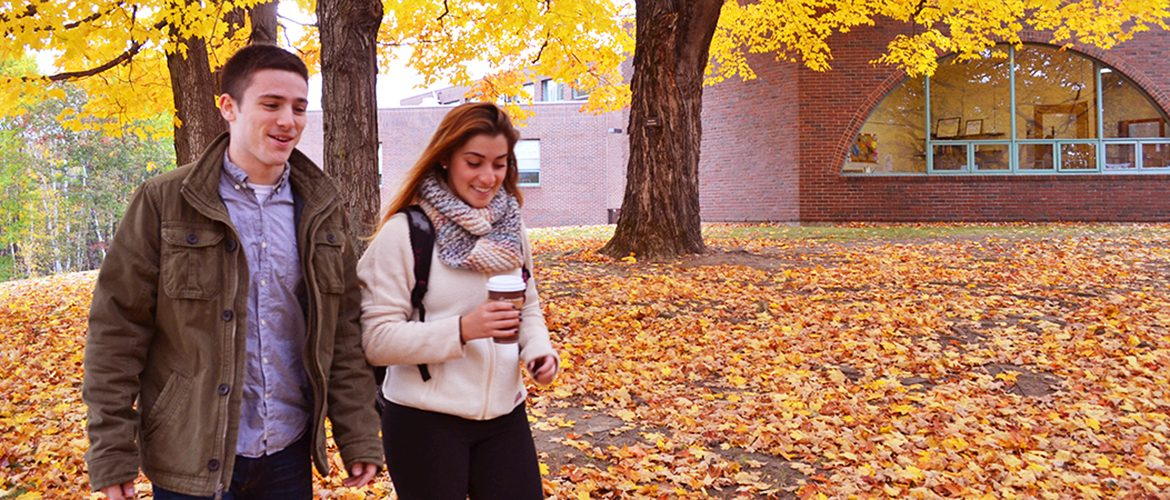Two students walking in leaves on campus