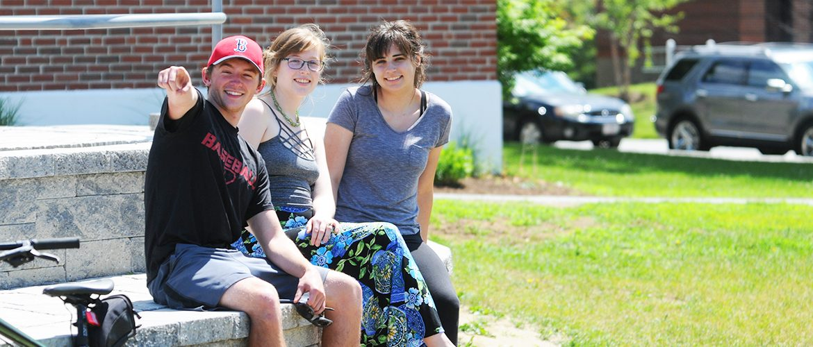 Three students sitting at the Mantor Library patio in the summertime