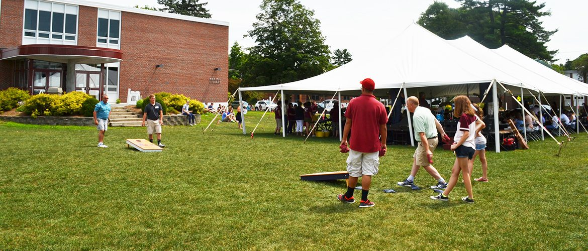 Scene from Summer Open House BBQ of guests playing corn hole on campus green