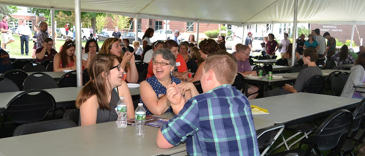 Scene from Summer Open House BBQ of professor talking with students under the tent
