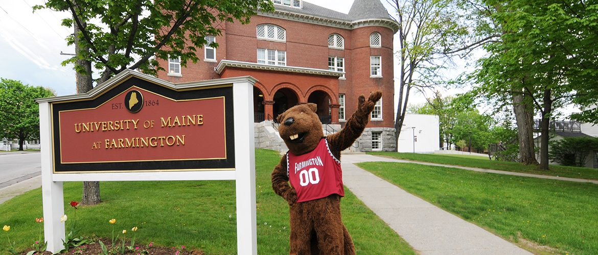 UMF Chompers beaver mascot standing in front of Merrill Hall
