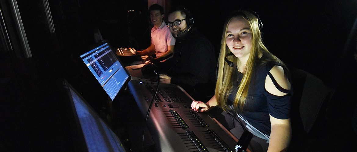 Student workers in theater light and sound control room