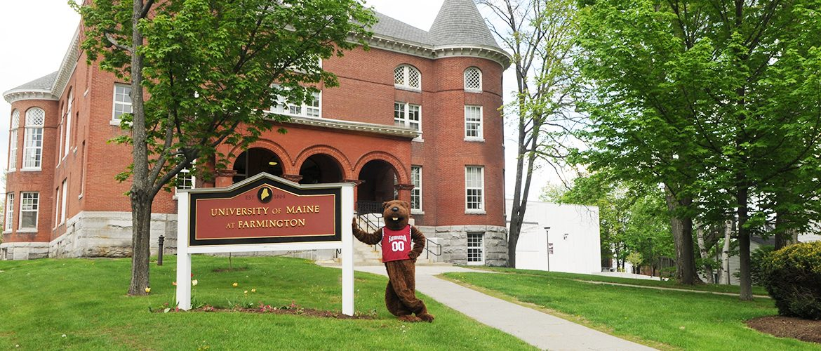 Beaver mascot standing near school sign in front of Merrill Hall