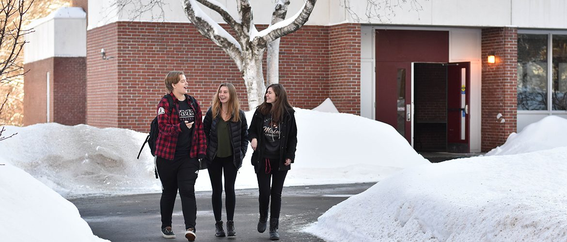 Three students walking through the campus courtyard in the snow