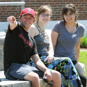 Three students hanging out on the campus green