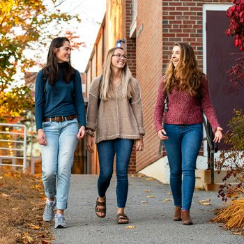 Three students walking across campus in the fall foliage