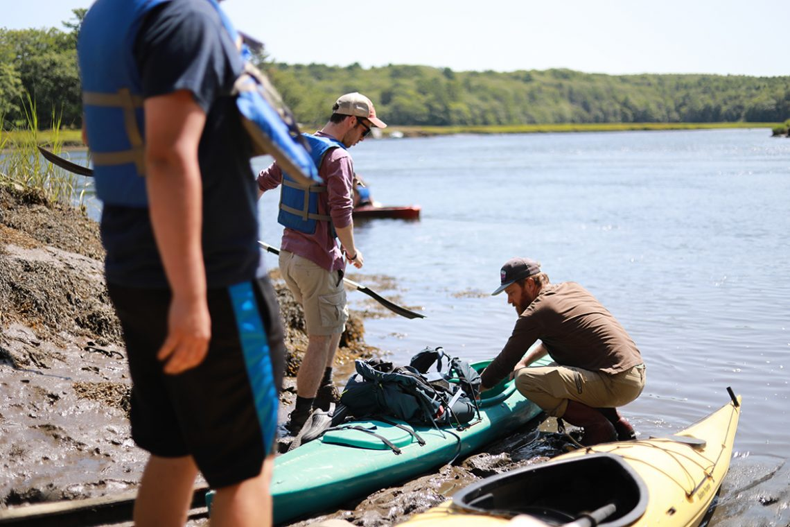 Philip Francis helps students load their kayaks for a paddle out to Perkins Island.