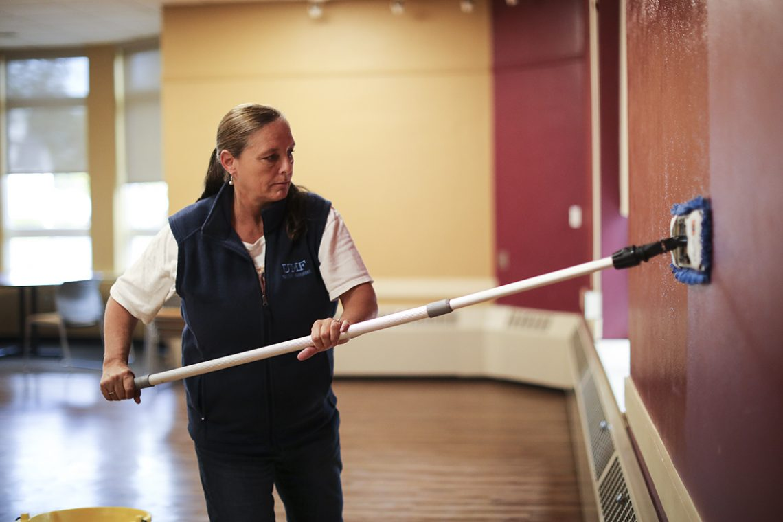 UMF Facilities Maintenance Lead Worker Laura Adams washes the walls.