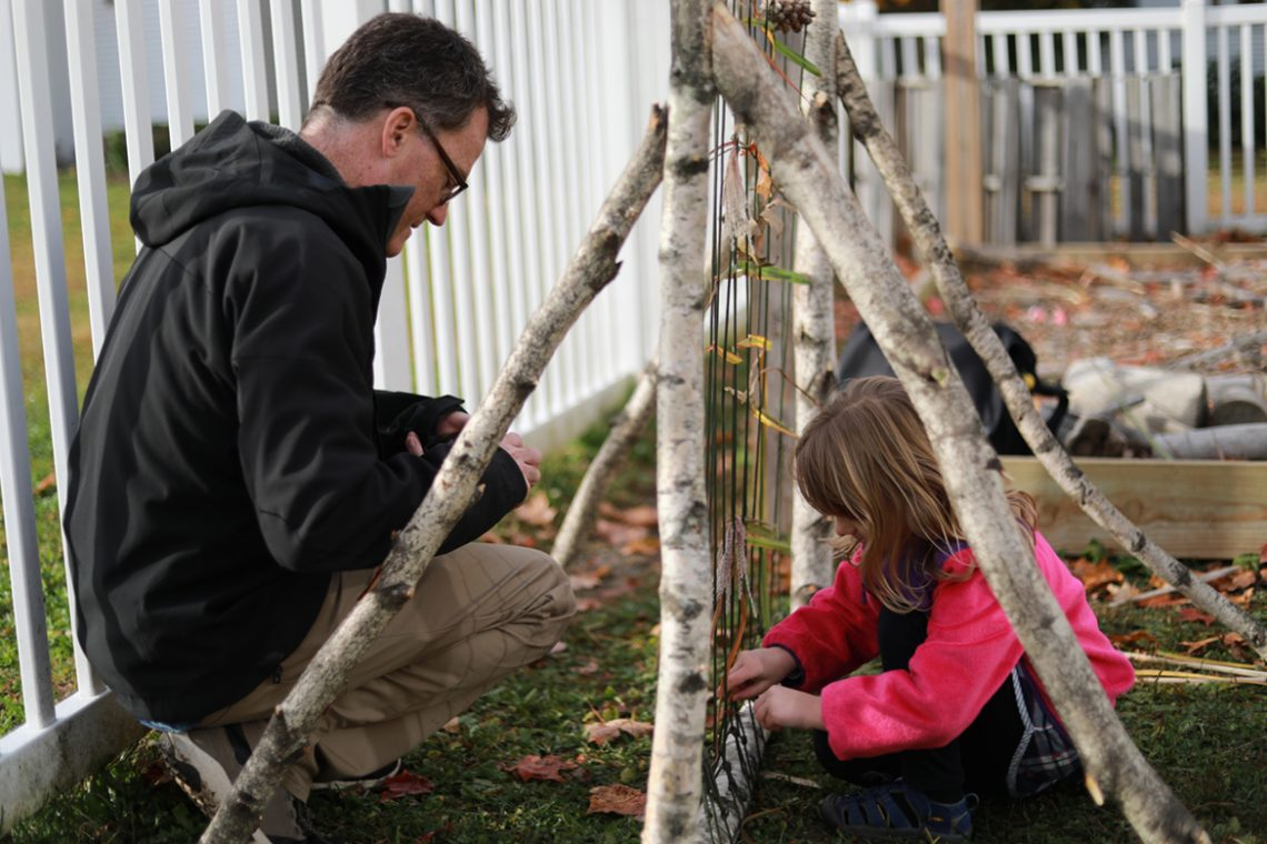 Matt McCourt assists a Sweatt-Winter student use a weaving loom designed by his students.