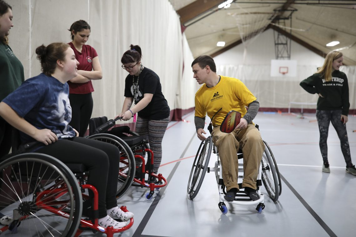 Brandon Merry instructs students in the use of sport chairs.