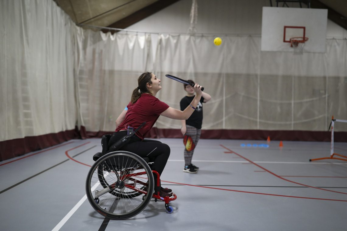 Emily Thompson plays pickleball while using a wheelchair.