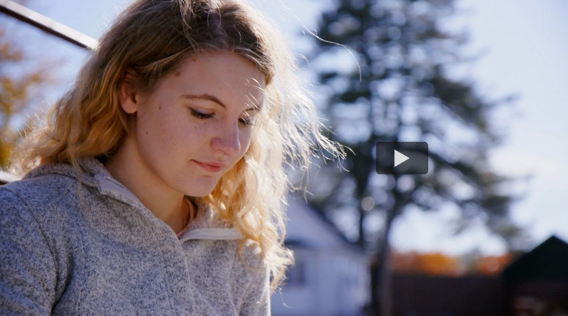 Student looking down reading. A videoplay button is overlayed.