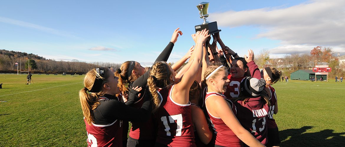 Women's varsity field hockey team carrying trophy