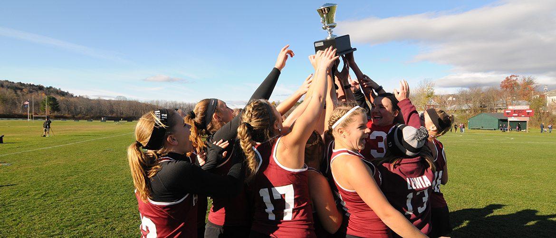 Women's varsity field hockey team carrying trophy