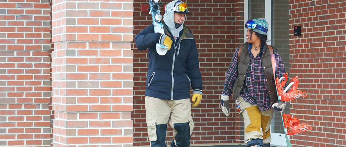 Students leaving residence hall with skis and snowboard