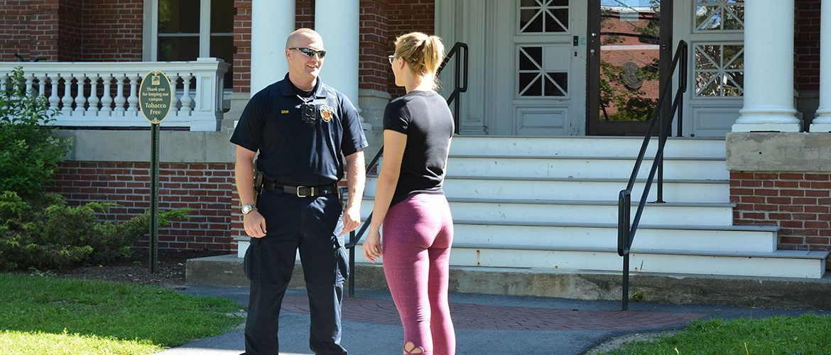 Female student talking with campus police officer in front of residence hall building