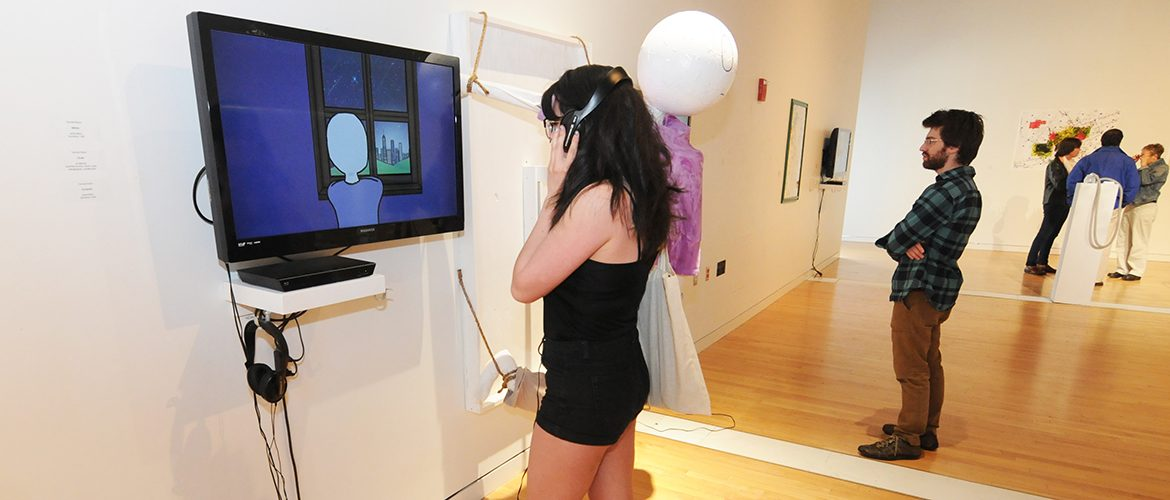 Student at an art exhibit in the Emery Community Arts Center