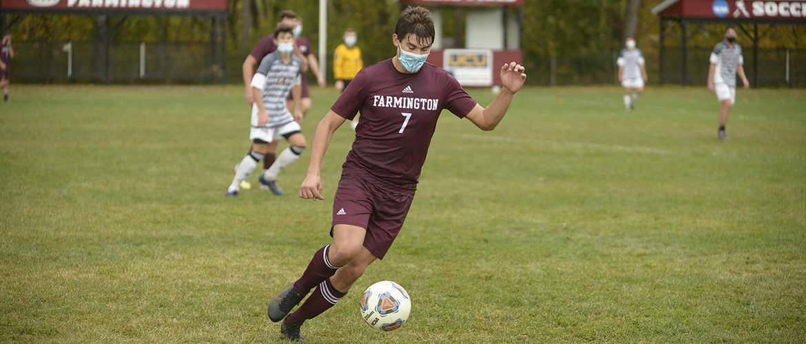 Male soccer player wearing a mask
